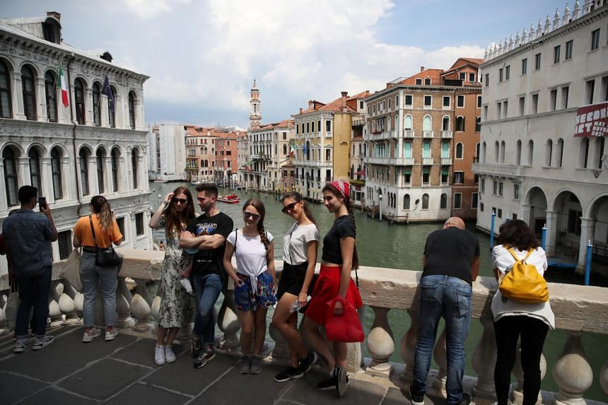 Tourists pose for a picture at the Rialto Bridge, in Venice, Italy, on June 7, 2021.