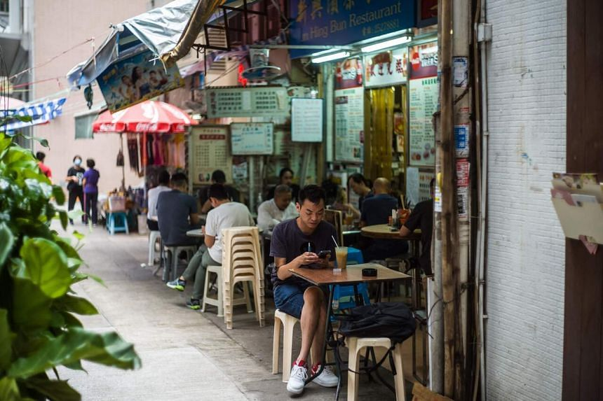 Customers eat at a street-side restaurant in the Wanchai district of Hong Kong, on June 21, 2021.