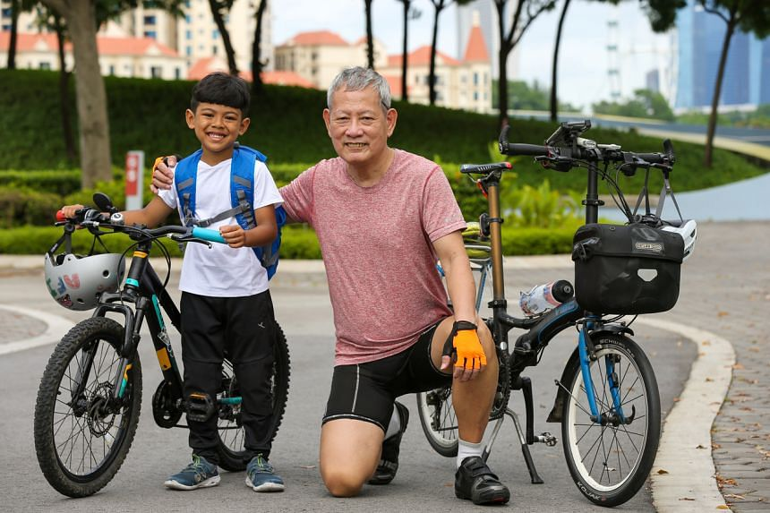 Avid cyclist Loh Yew Kwong gave Muhammad Afi (left) an OCBC Ride 2021 medal to encourage him after the latter's personal achievement was shared on Facebook.