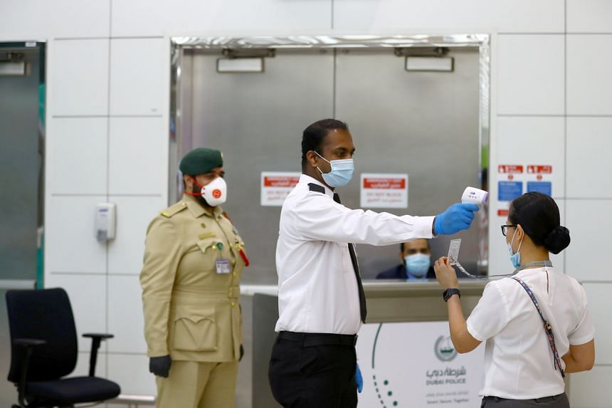 A security man takes temperature of a woman at the Dubai International Airport, UAE, on April 27, 2020.