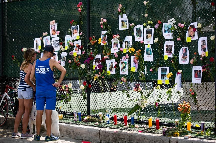 People mourn at the memorial site in front of the partially collapsed  Champlain Tower South building in Surfside, Florida, on June 26, 2021.