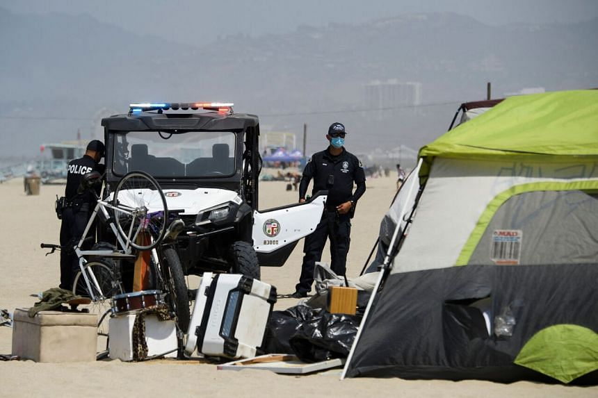Police officers are seen at a beach encampment where homeless people are staying, in Los Angeles on June 16, 2021.