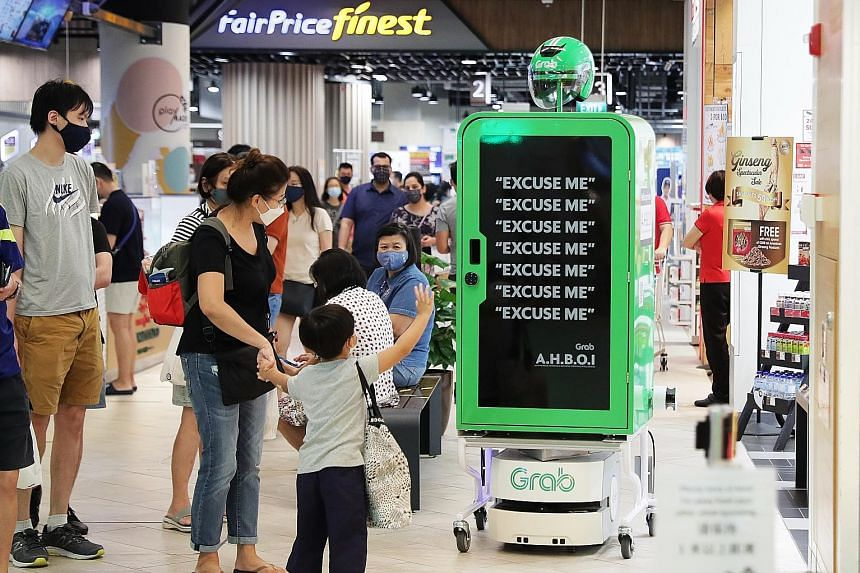 """Visitors to Paya Lebar Quarter mall may run into a new kind of deliveryman - and a very polite one at that. Named AHBOI (Autonomous Handling & Batching Operating Intelligence), the """"robot runner"""" was launched by Grab to help consolidate GrabFood orde"""