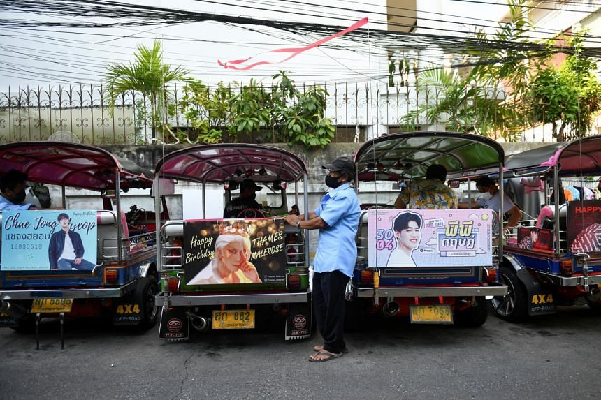 Tuk-tuk drivers, with their vehicles decorated with banners of Thai and South Korean stars, in Bangkok on May 12, 2021.