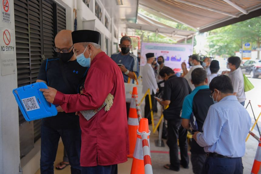 A staff checking whether a congregant has been fully vaccinated as he enters Masjid Mujahidin on June 25, 2021.