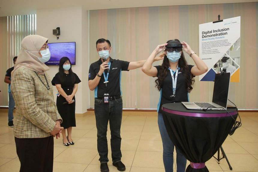 President Halimah Yacob watching a demonstration of how the Mixed Reality HoloLens allows experts to remotely assist on-site technicians in troubleshooting.