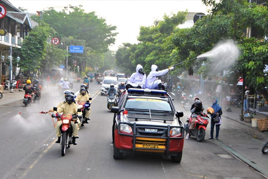 Health workers disinfect a street in Solo, Indonesia, on June 25, 2021.