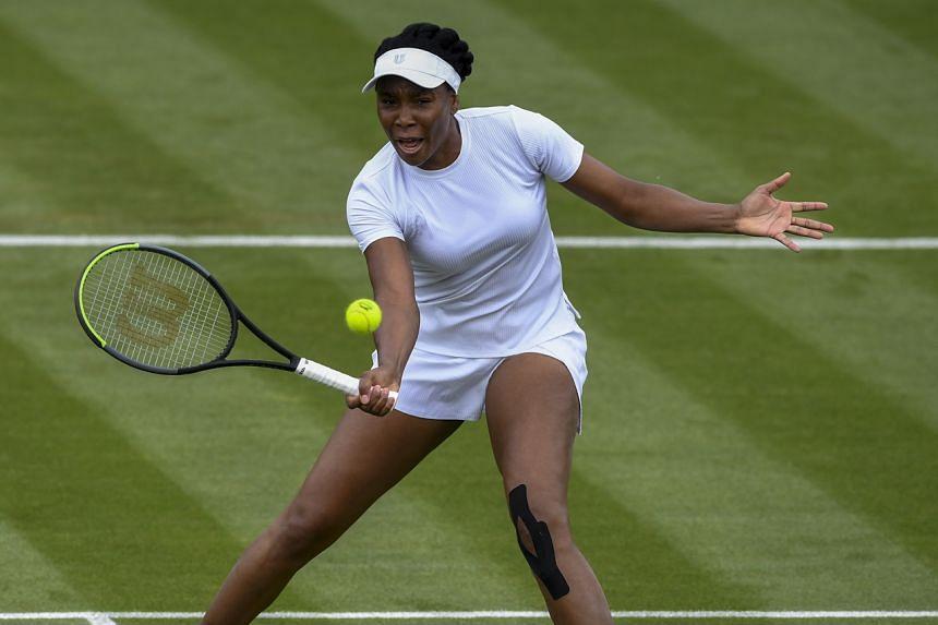 Venus Williams hitting a shot against Mihaela Buzarnescu during their match at Wimbledon on June 29, 2021.