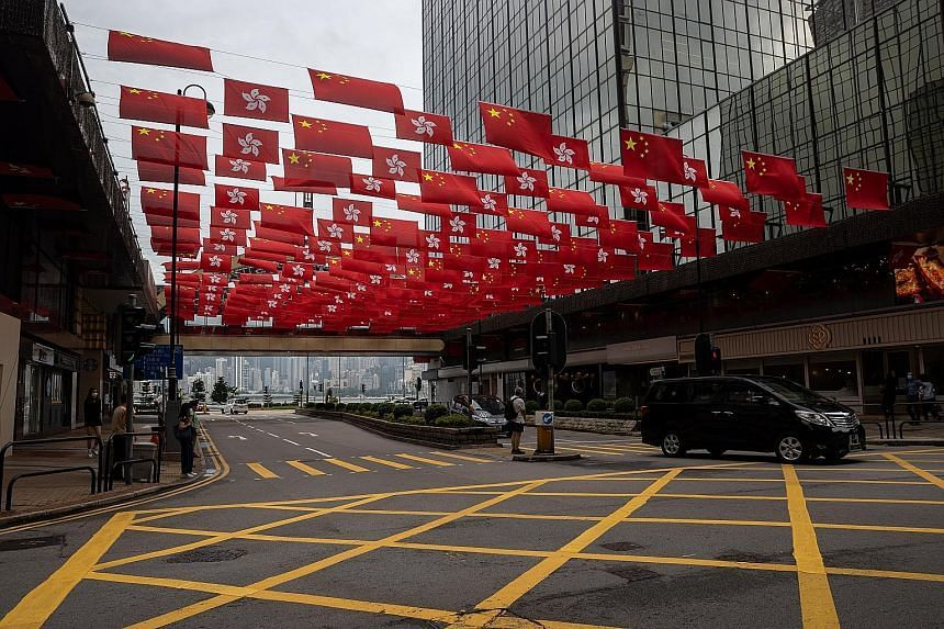 Flags of the People's Republic of China and the Hong Kong Special Administrative Region on display along a street in Hong Kong on June 28, 2021.