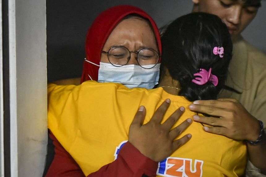 Passengers embrace as they arrive at a port in Banyuwangi, East Java, after the accident in Bali's Gilimanuk port.