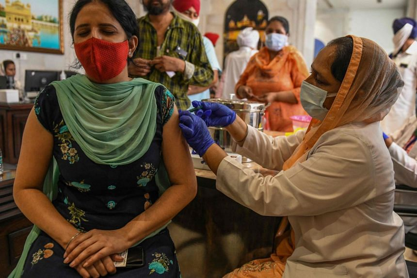 A health worker inoculates a woman with a coronavirus vaccine dose in Amritsar, India, on June 29, 2021.