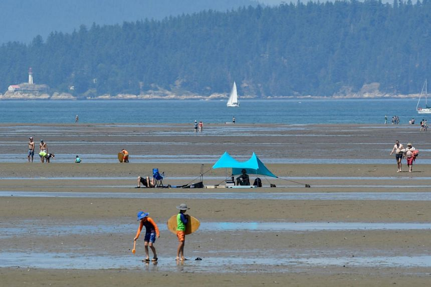 People are seen at a beach during a heat wave in Vancouver on June 27, 2021.