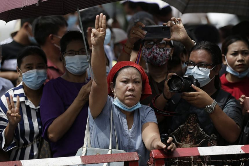 A woman flashes the defiant three-finger salute as people wait behind barricades for their relatives to be released outside the main entrance of Insein prison compound in Yangon, Myanmar, on June 30, 2021.