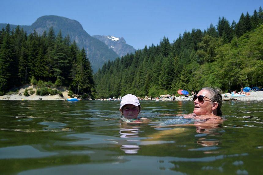 Kim Cullen and her granddaughter Ella cool off in Alouette Lake, in Maple Ridge, British Columbia, on June 28, 2021.