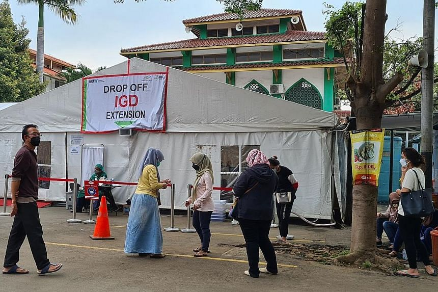 Jakarta residents waiting for their family members to be examined at a tent which Pelni Hospital has turned into its emergency unit due to a surge of Covid-19 patients. Many families of Covid-19 patients are struggling to find hospital beds as bed oc