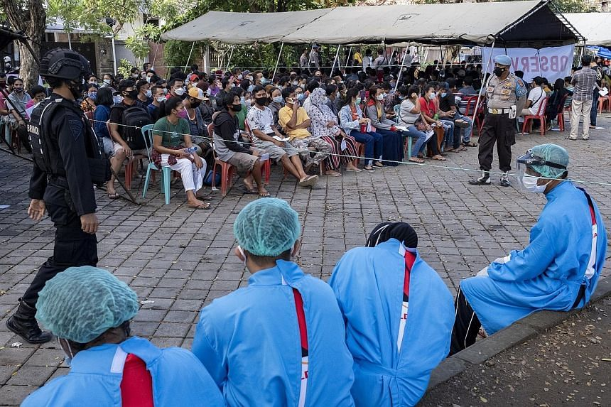 People waiting their turn during a mass vaccination drive in Denpasar, Bali, late last month. Java and Bali have about 1.52 million cases, or 70 per cent of the total number of cases in Indonesia. Workers wearing personal protective equipment lowerin