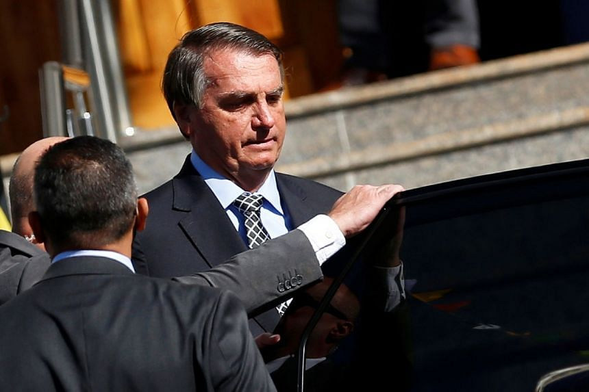 Brazil's President Jair Bolsonaro gets into a vehicle after attending mass at a Catholic church in Brasilia, on July 1, 2021.