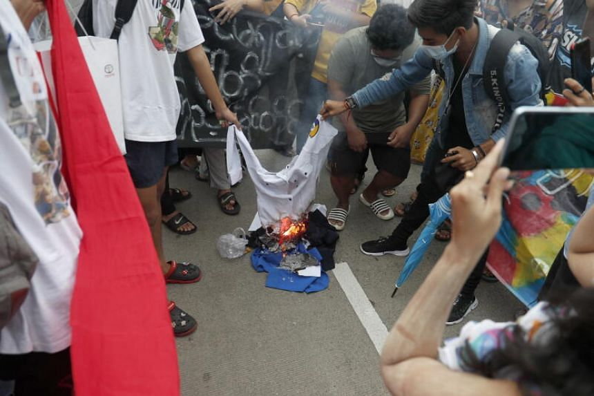Demonstrators burning a portrait of Military chief Min Aung Hlaing and traffic police uniform during an anti-military coup protest in Yangon, Myanmar on July 3, 2021.