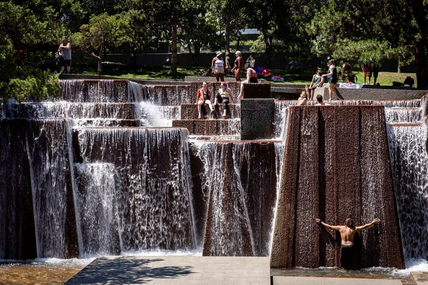 People cooling off in a public fountain during an unprecedented heat wave in Portland, Oregon, on June 27, 2021.