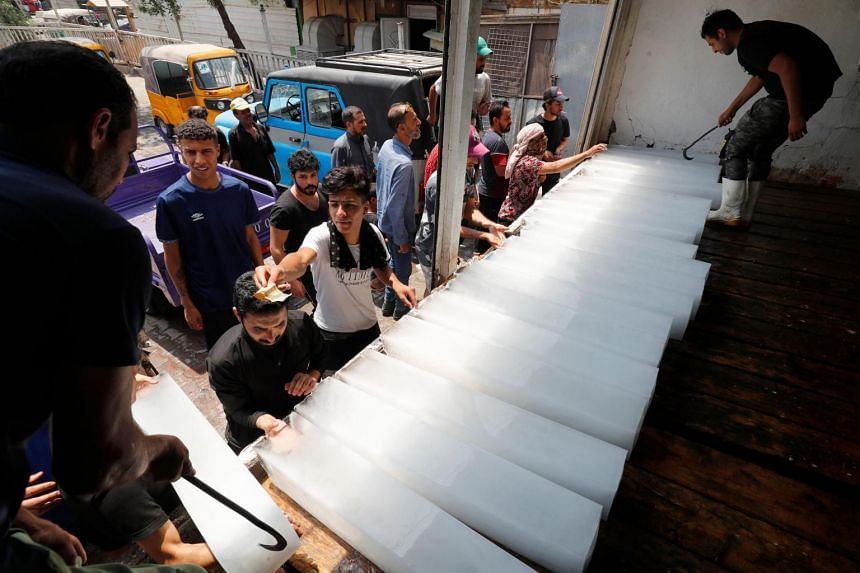 Iraqis buying ice blocks at a factory in Sadr City, east of the capital Baghdad, on July 2, 2021, amid power outages and soaring temperatures.