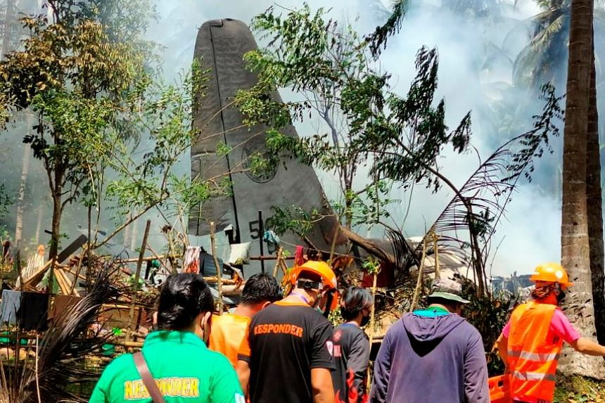 First responders work at the site after a Philippines Air Force Lockheed C-130 plane crashed on landing in Patikul, Sulu province, Philippines, on July 4, 2021.