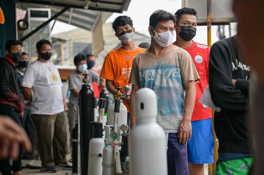 Indonesians queue at an oxygen filing shop to fill tanks for sick family members in Jakarta, on June 30, 2021.