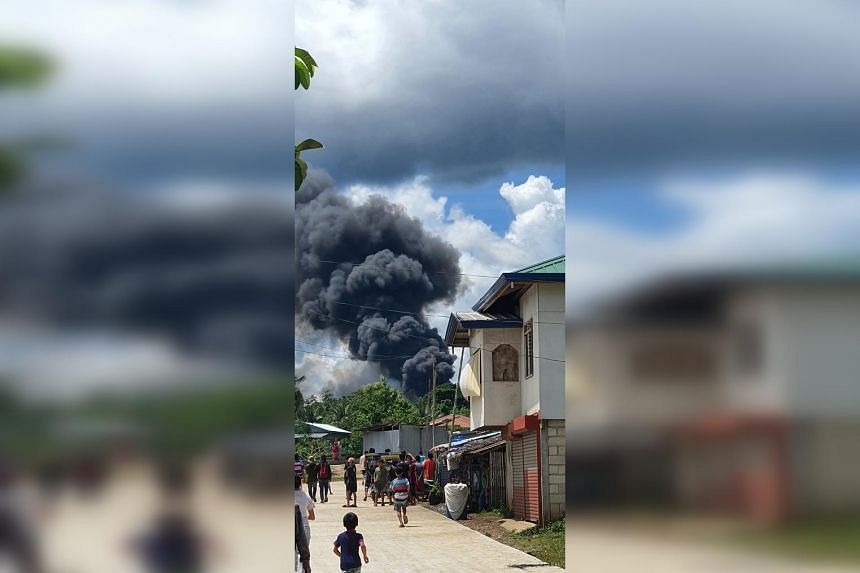 Residents gather as smoke rises from the wreckage after a Philippines Air Force Lockheed C-130 transport plane crashes on landing in Patikul, Sulu province, Philippines, on July 4, 2021.