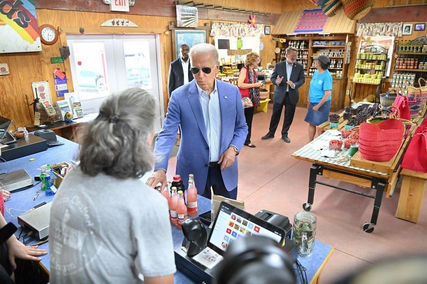 US President Joe Biden buys products at a market in Central Lake, Michigan on July 3, 2021.