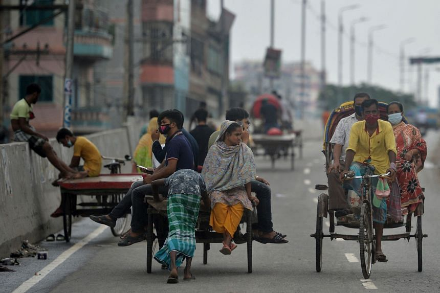Commuters make their way along a road on cycle-rickshaw during the lockdown imposed to contain the spread of Covid-19 in Dhaka, on July 4, 2021.