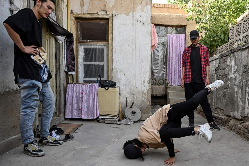 Manizha Talash (centre) practices a move as two members of her breakdance troupe look on in Kabul, on June 12 2021.