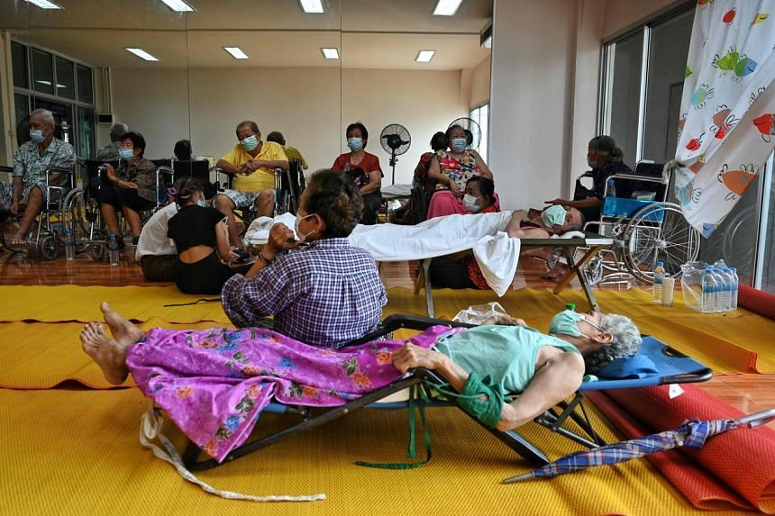 Residents resting at Wat Bang Phli school on the outskirts of Bangkok, after they were evacuated following an explosion at a plastics factory, on July 5, 2021.