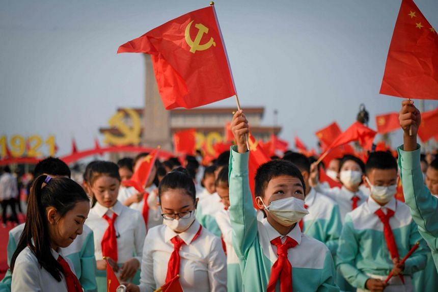 A student waves the flag of Communist Party of China in Beijing on July 1, 2021.