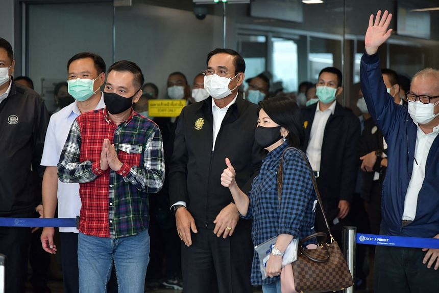Thailand's Prime Minister Prayut Chan-O-Cha (centre) posing for a photo with incoming travellers at Phuket International Airport on July 1, 2021.