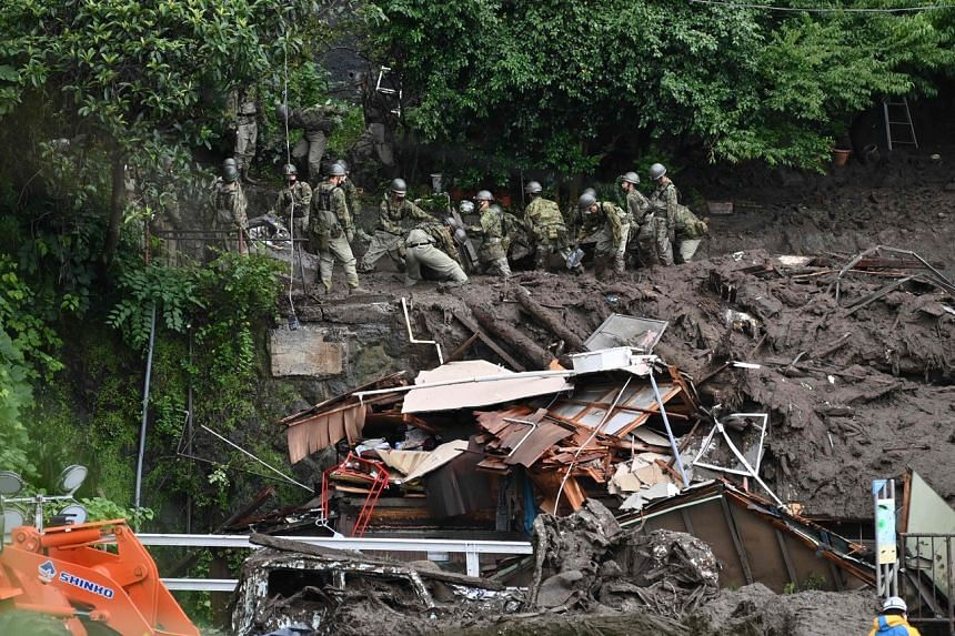 Members of Japan's Self-Defence Forces sift through mud and debris as they search for missing people in Atami on July 5, 2021.