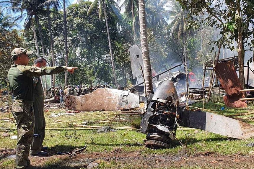 Members of the Philippine military at the scene of the crash in Sulu province on Sunday. The Lockheed C-130 military transport plane was carrying 96 soldiers, including three pilots.