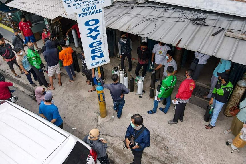 Indonesians queueing at an oxygen filing shop to fill tanks for sick family members in Jakarta, on June 30, 2021.