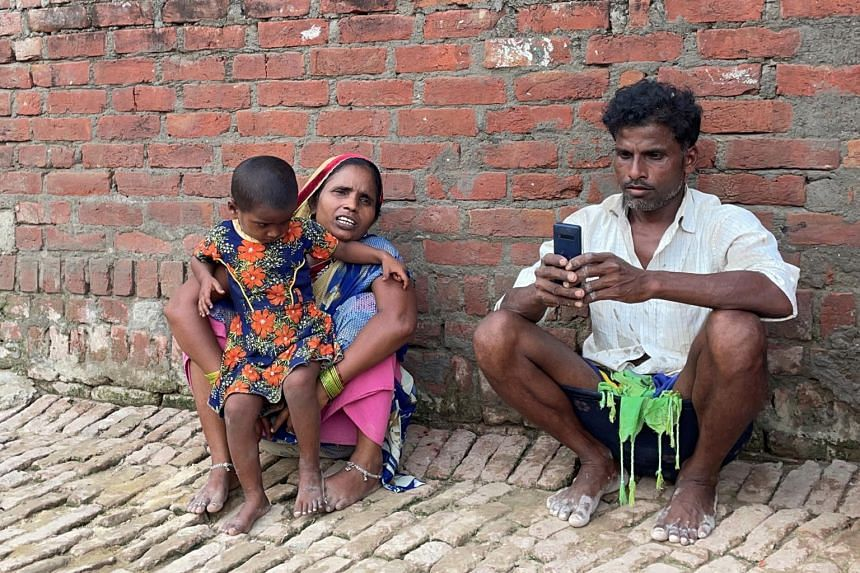 Ms Asha Devi with her husband and their daughter outside her one-room house in Dihwa village in the northern state of Uttar Pradesh on June 22, 2021.