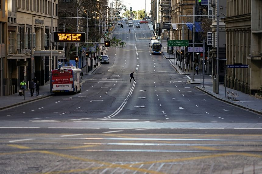 A pedestrian crosses an unusually quiet street in the city centre during a lockdown in Sydney on July 5, 2021.