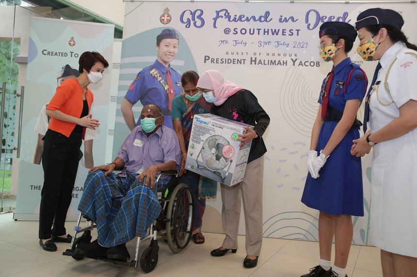 Mayor of South West district Low Yen Ling (left) and President Halimah Yacob (centre) present S Periyaswamy with a portable fan.