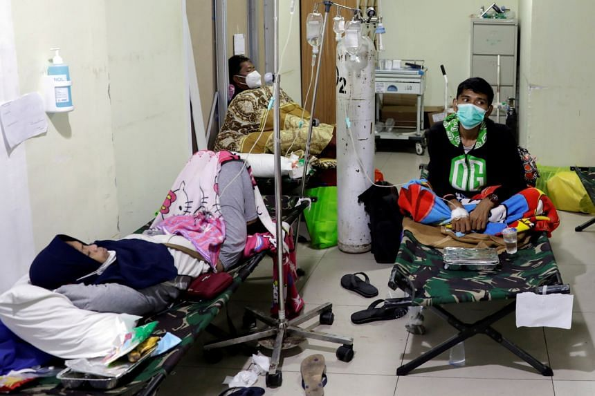 People rest on veld beds inside the emergency ward for Covid-19 patients at a government-run hospital in Jakarta, on June 29, 2021.