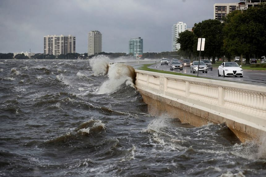Waves crash against the balustrades on Bayshore Boulevard during high tide after Tropical Storm Elsa churns up the Gulf coast, in Tampa, Florida.