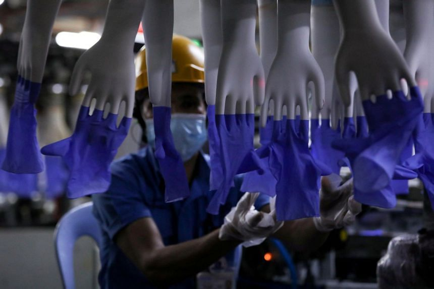 A worker inspecting newly made gloves at Malaysian company Top Glove's factory in Shah Alam last year.