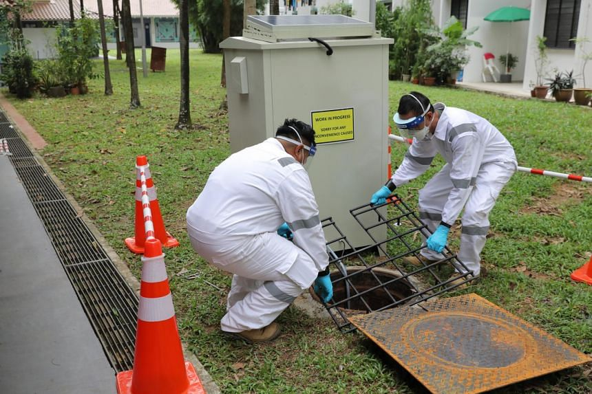 National Environment Agency officers preparing a manhole for wastewater surveillance on July 7, 2021.