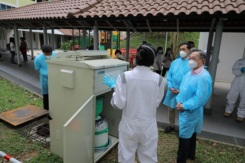 Mr Gan Kim Yong (right) and Mr Ong Ye Kung visiting a site on NEA's wastewater surveillance programme.