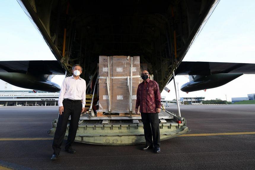 Dr Vivian Balakrishnan (left) with Indonesia's Ambassador to Singapore Suryo Pratomo during the handover of the assistance package at Paya Lebar Air Base.