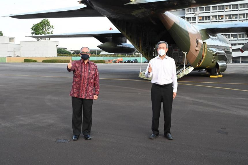 Dr Vivian Balakrishnan (right) with Indonesia's Ambassador to Singapore Suryo Pratomo (left) during the handover of the assistance package at Paya Lebar Air Base earlier today.