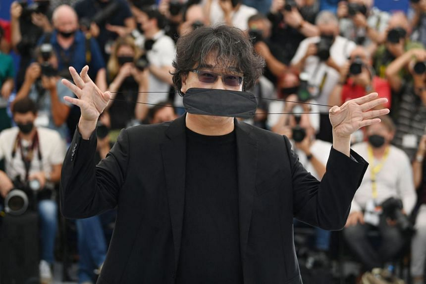 South Korean director Bong Joon-Ho plays with his face mask during a photocall for the Rendez-Vous With, in Cannes, on July 7, 2021.