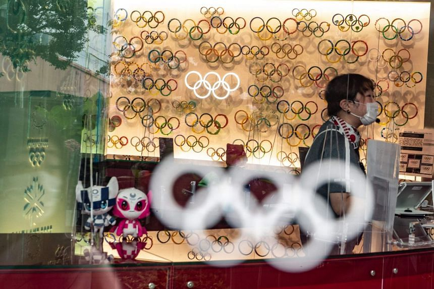 An employee is seen among Olympic Rings and Tokyo 2020 mascots at the Japan Olympic Museum in Tokyo on July 8, 2021.