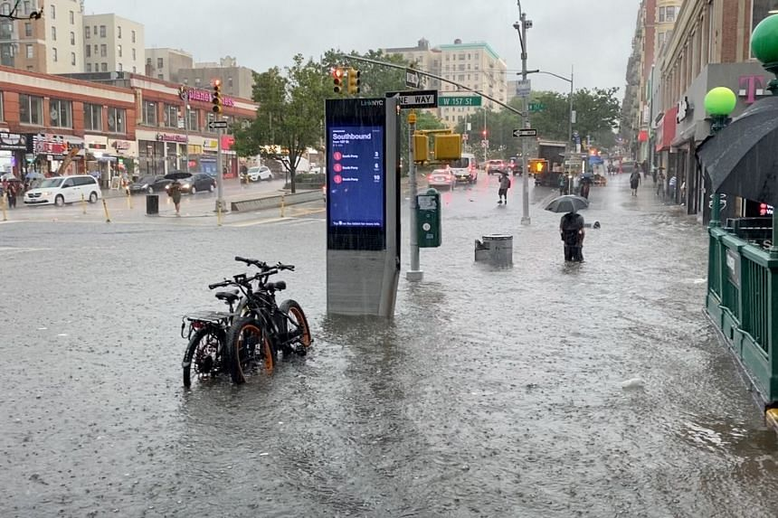 A person wades through flood water near the 157th Street subway station in New York City on July 8, 2021.