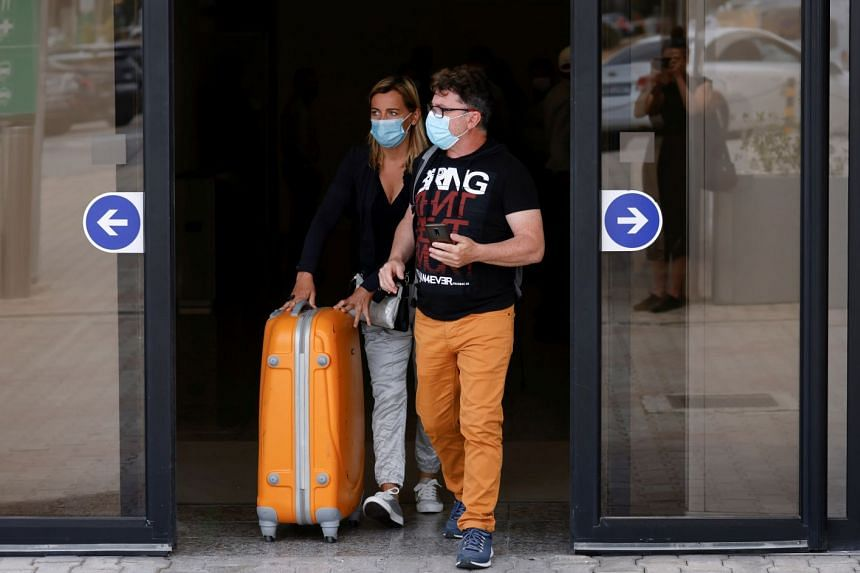 Tourists walk out of the arrivals terminal after arriving at Malta International Airport on June 1, 2021.